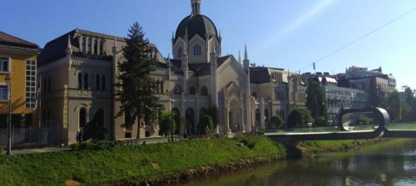 Budynek Akademii Sztuk Pięknych w Sarajewie nad rzeką Miljacka. Prowadzi do niego most Festina Lente.