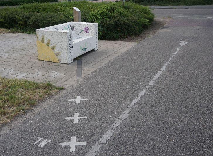 Granica biegnąca przezścieżkę rowerową isymboliczna ławka